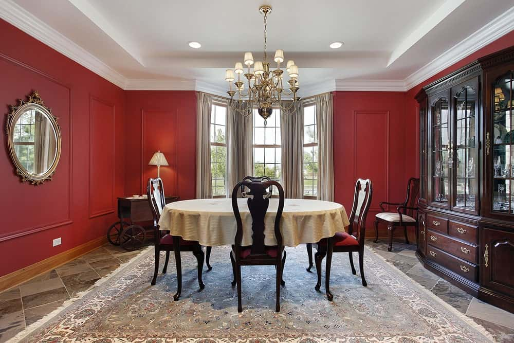 Red dining room with white tray ceiling, wainscoted walls, tiled flooring topped by a printed rug, dark wood display cabinet, white framed windows covered in beige drapes, an ornate wall mirror and a round dining set illuminated by a chandelier.