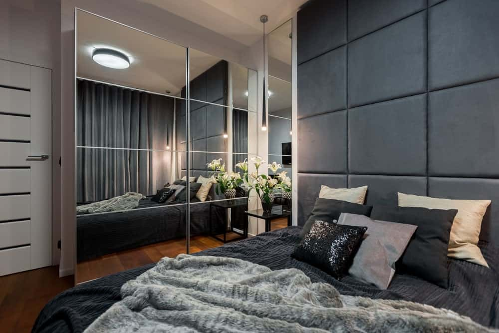 Apartment master bedroom with rich hardwood flooring, paneled mirrors and a comfy bed with a large custom headboard.