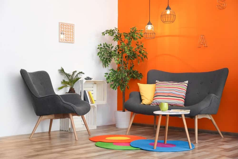 Modern living room with white and orange walls, gray seats, fresh potted plants, white shelving, a round coffee table and colorful rugs over hardwood flooring.