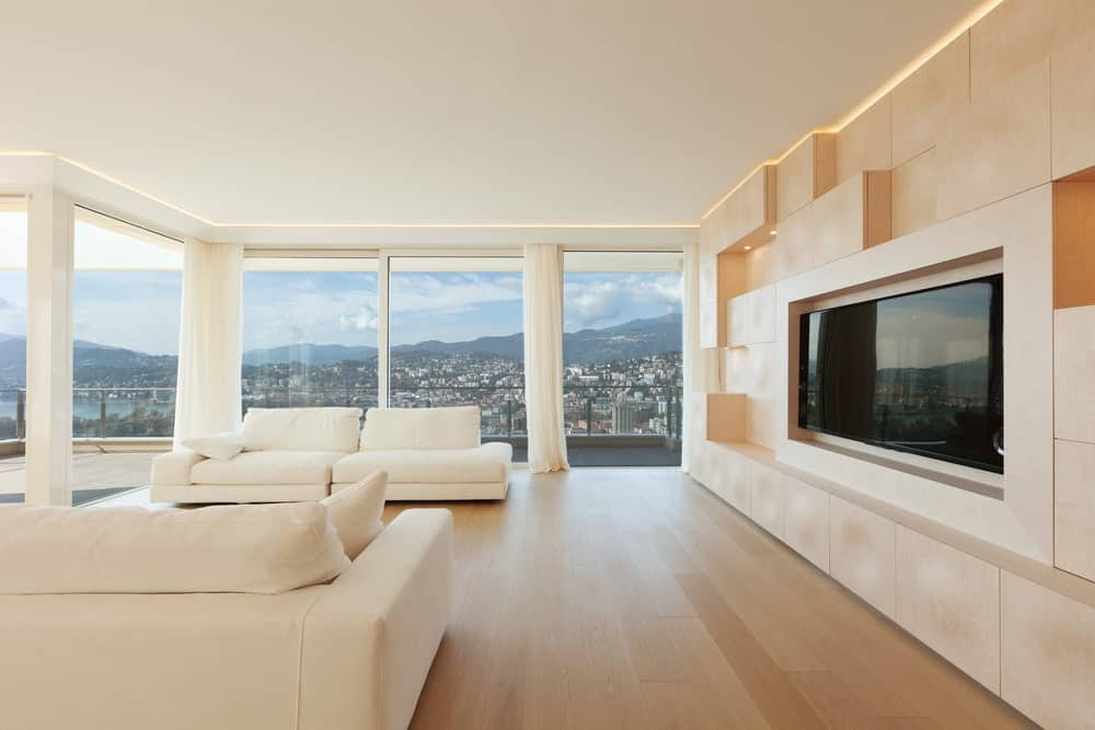 Minimalist living room with white comfy seats, wall TV, light hardwood flooring and full height windows framing a mesmerizing view.