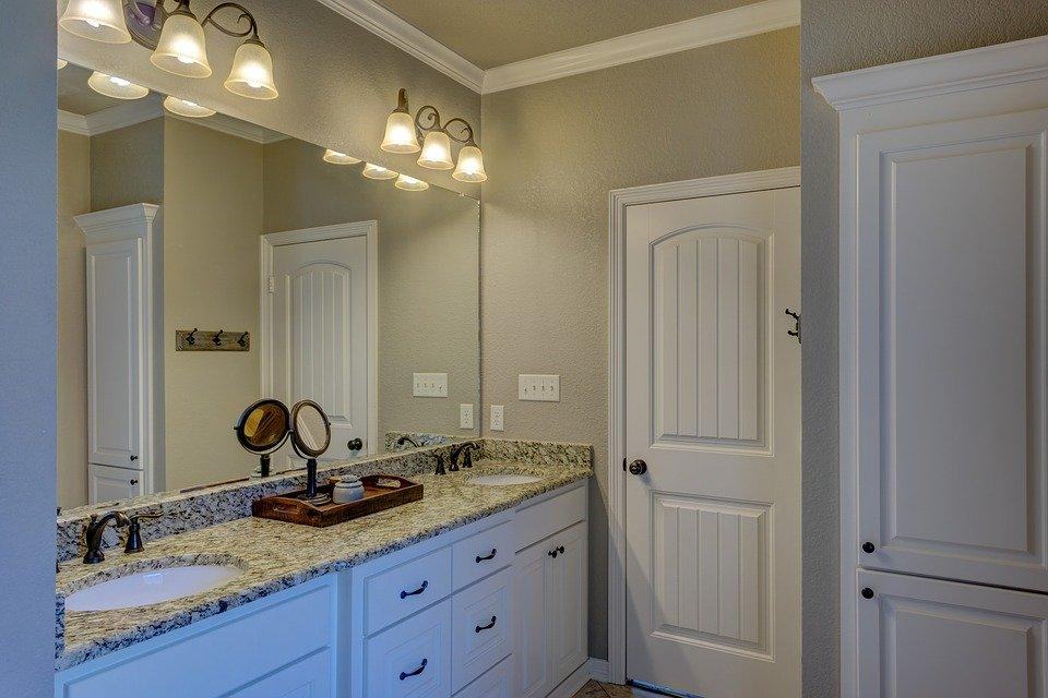 Classic designed bathroom with dark gray painted wall, large mirror and vanity with marble top