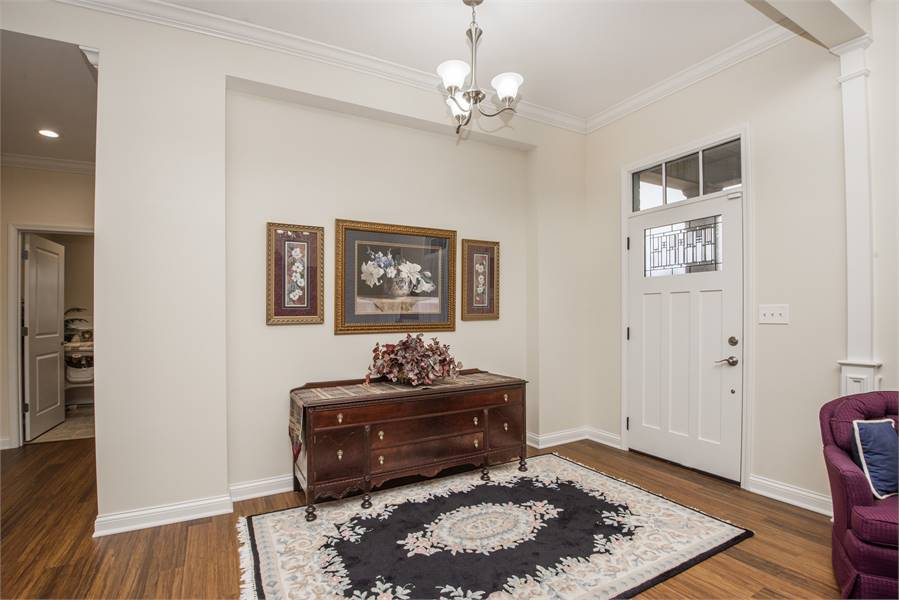 The foyer with a white front door and an antique console table complemented with a classic rug.