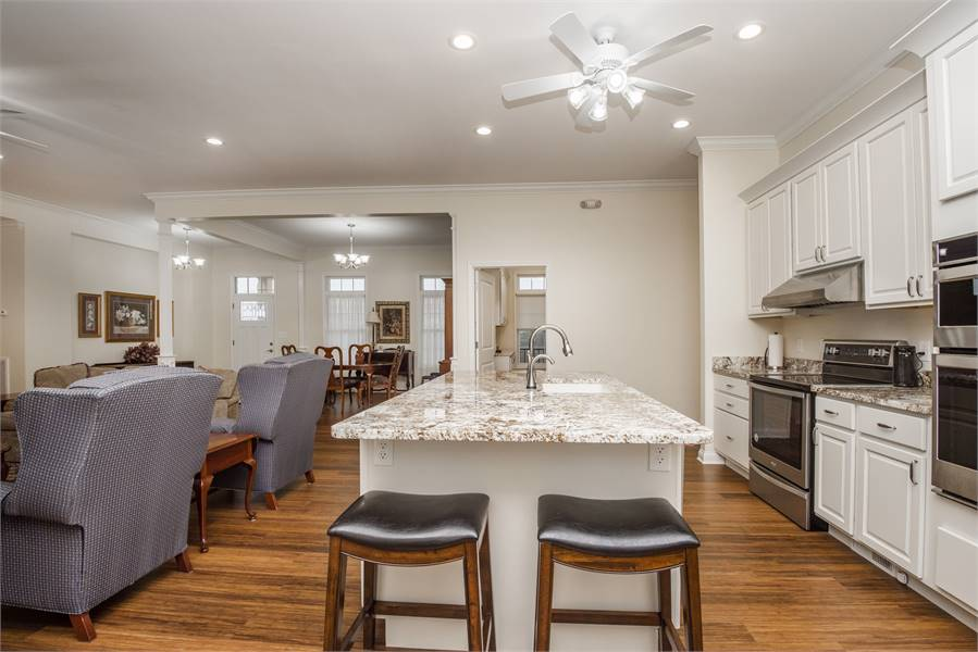 A pair of leather cushioned stools complement the granite top island.