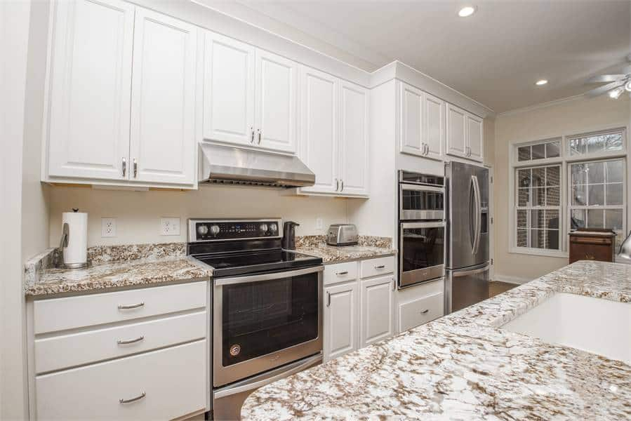 The kitchen is equipped with cutting-edge appliances and pristine white cabinetry.