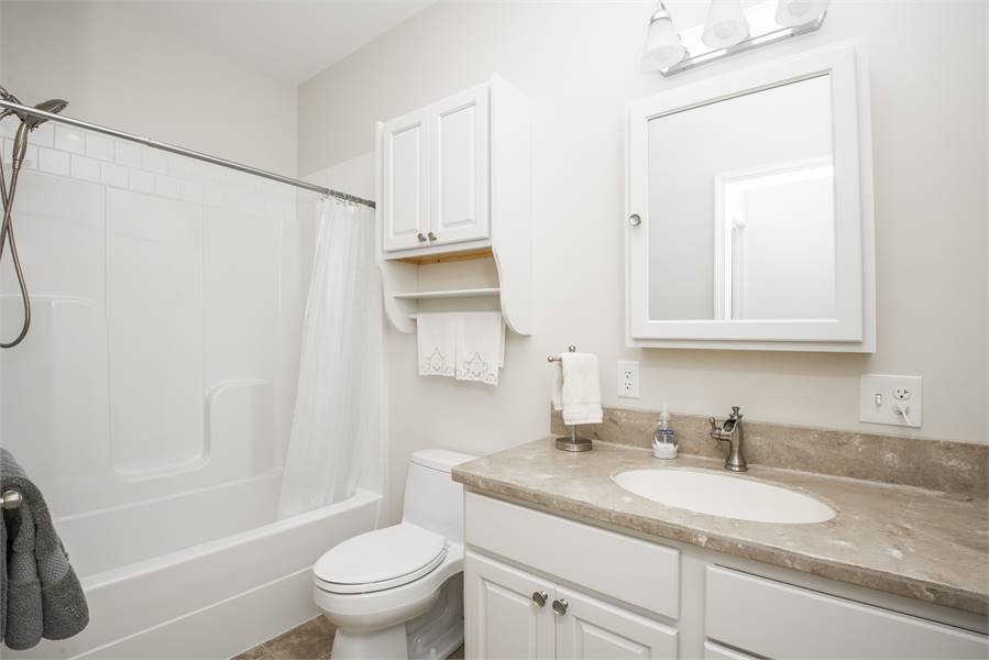 Bathroom with a sink vanity, a toilet under a floating cabinet, and a tub and shower combo.