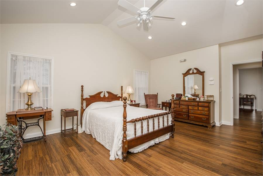 The master bedroom has a four-poster bed and a lounge chair sitting next to the vanity dresser.