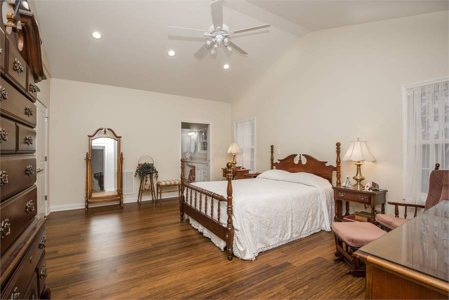 Opposite side view of the master bedroom with rich hardwood flooring and a cathedral ceiling mounted with a white fan.