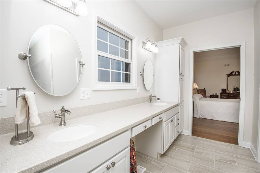The master bathroom includes a lengthy dual sink vanity paired with round mirrors and chrome sconces.