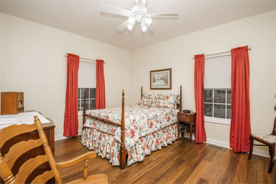 The other bedroom showcases a skirted bed and white framed windows dressed in red curtains.