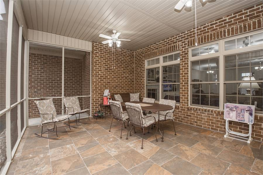 The rear porch covered in screen panels. It is filled with metal cushioned chairs, an oval table and ceiling white fixed on the shiplap ceiling.