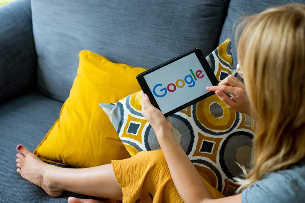 A woman using Google on her small tablet.