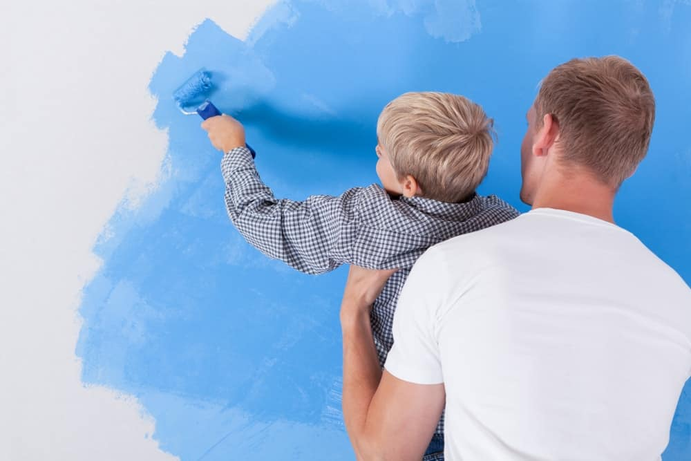 A man and his son painting the wall with blue paint.
