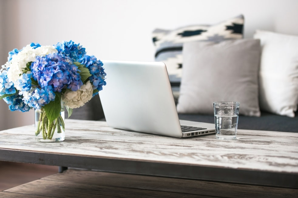 7 Simple Ways to Freshen Up Your Home This Spring. Polished wooden coffee table and the glass vase to decorate the improvised working space