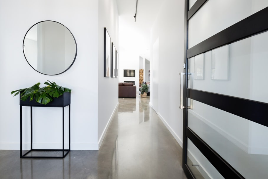 Classy white and natural light lit corridor of the house with black framed interior doors