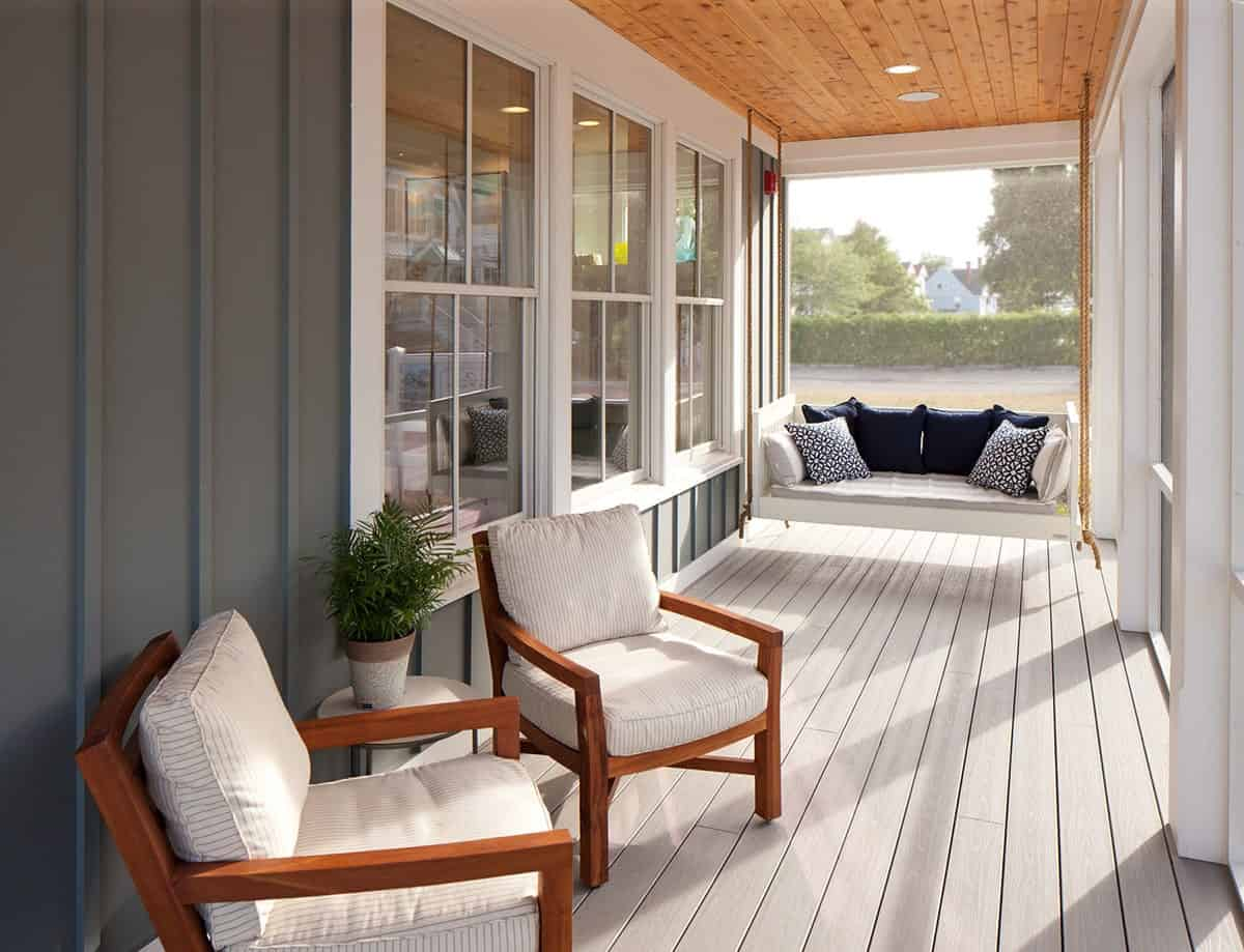The screened porch offers cushioned armchairs and a hanging swing bench filled with blue pillows.