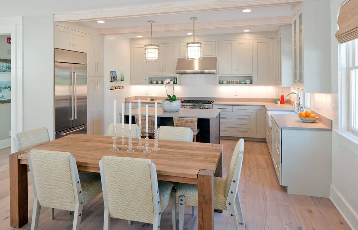 Eat-in kitchen with white cabinetry, a breakfast island bar, and a wooden dining table paired with charming patterned chairs.