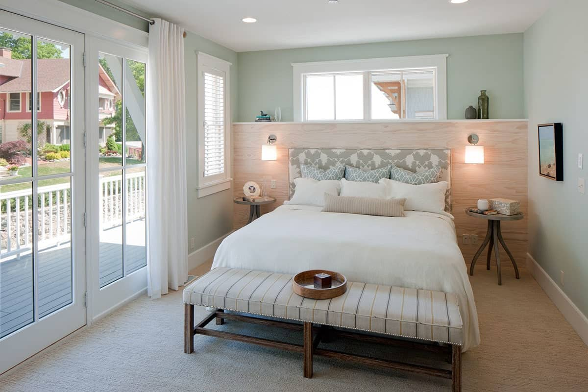 Master bedroom with a striped bench and cozy bed flanked by round nightstands and glass sconces mounted on the wooden headboard.