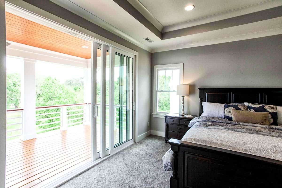 The master bedroom has gray walls, carpet flooring, tray ceiling and sliding glass doors that lead out to the covered porch.