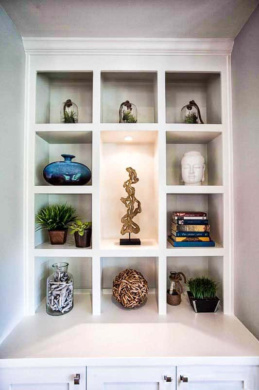 A closer look at the built-in shelves filled with books, potted plants, glass vases, and beautiful sculptures.