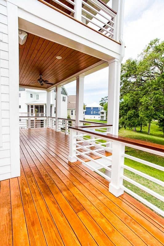 The rear porch is framed with sleek columns and white railings with polished handrails matching with the floor and ceiling.