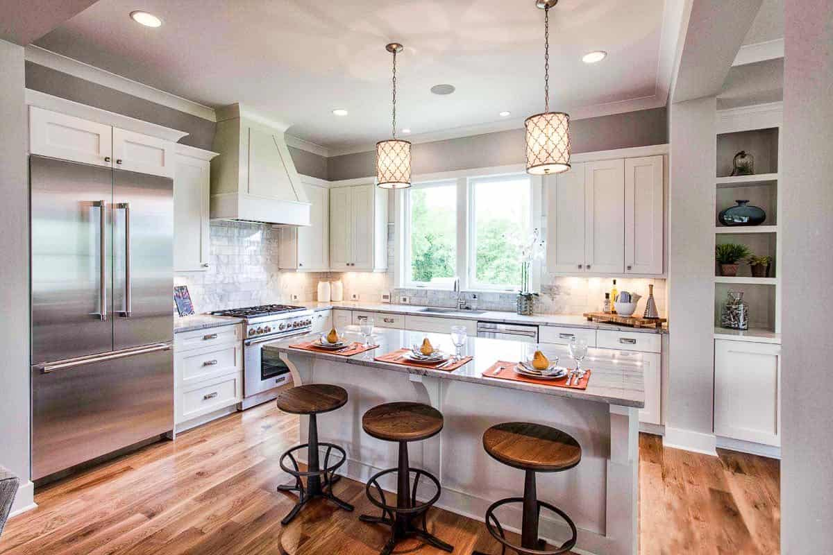 The kitchen is equipped with stainless steel appliances, white cabinetry, and a breakfast island complemented by round bar stools and a pair of glass pendants.