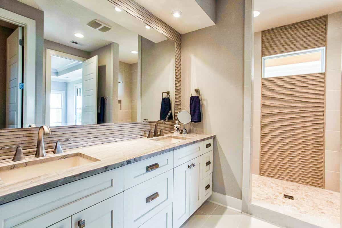 Master bathroom with a shower area, and dual sink vanity paired with a large frameless mirror.