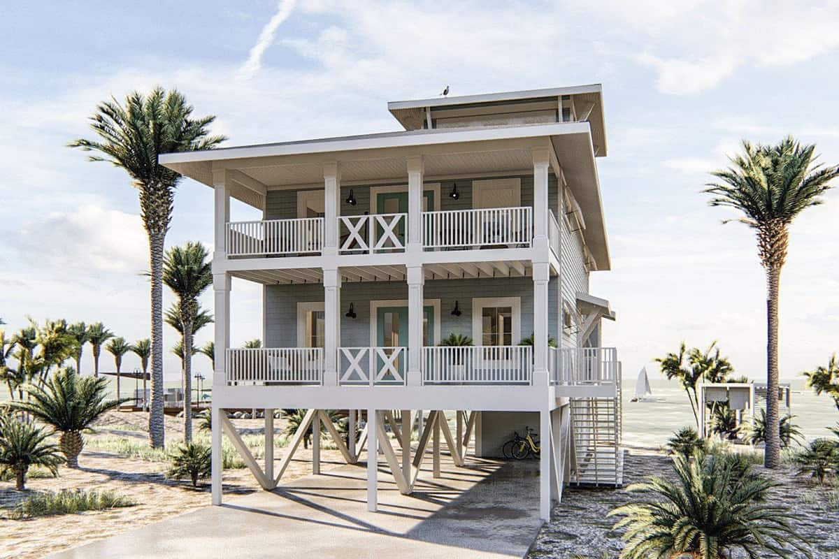 Home's rear view with covered porches framed with white railings and decorative columns. The surrounding palm trees add a marvelous appeal.