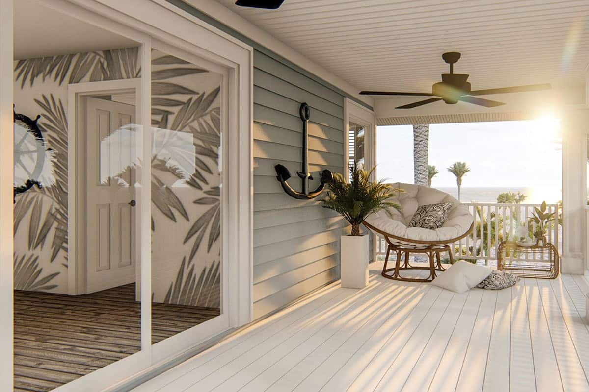 Covered deck filled with a round chair, metal side table, and fluffy pillows that lay on the white flooring.