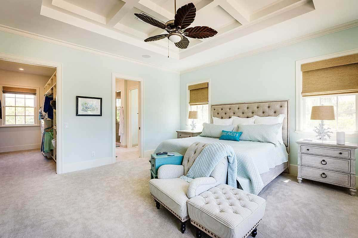 The master bedroom has a beige carpet flooring and a tray coffered ceiling mounted with a stylish fan.