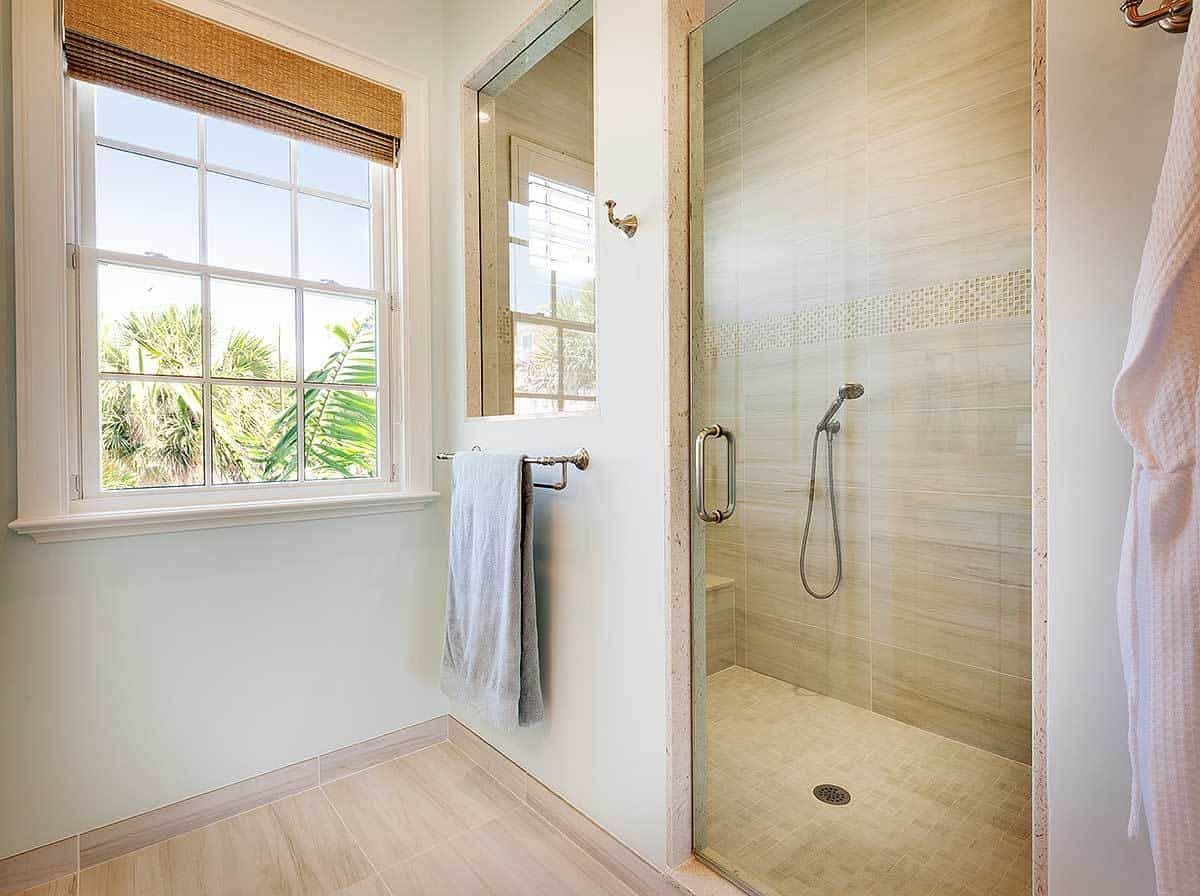 A closer look at the walk-in shower with tiled bench and a frameless glass window and door.