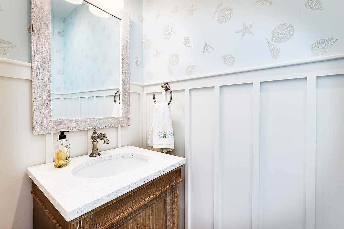 A powder room designed with a beach-themed wallpaper and white wainscoting.
