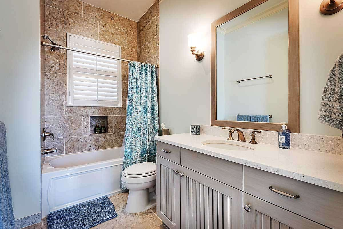 Guest's bathroom with a sink vanity, a toilet, and a shower and tub combo enclosed in a printed curtain.