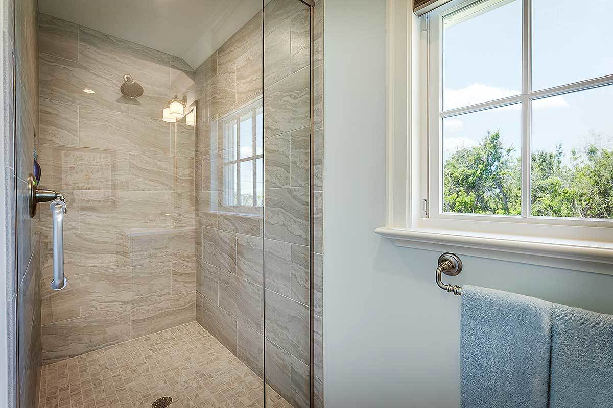 The opposite view shows the walk-in shower with marble tiled walls and chrome fixtures.