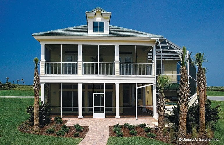 The rear view shows the screened porches with a dormer window on top. Brick paving and beautiful plants enhance the home's appeal.