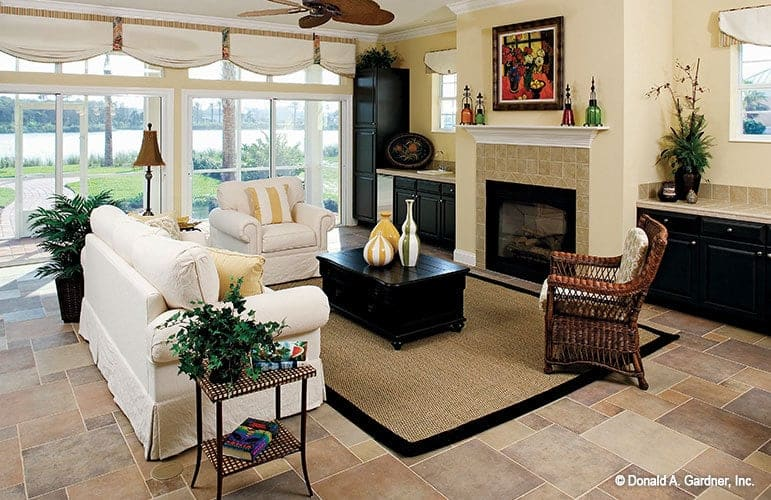The living room includes a warm fireplace under the lovely artwork flanked by built-in bars.