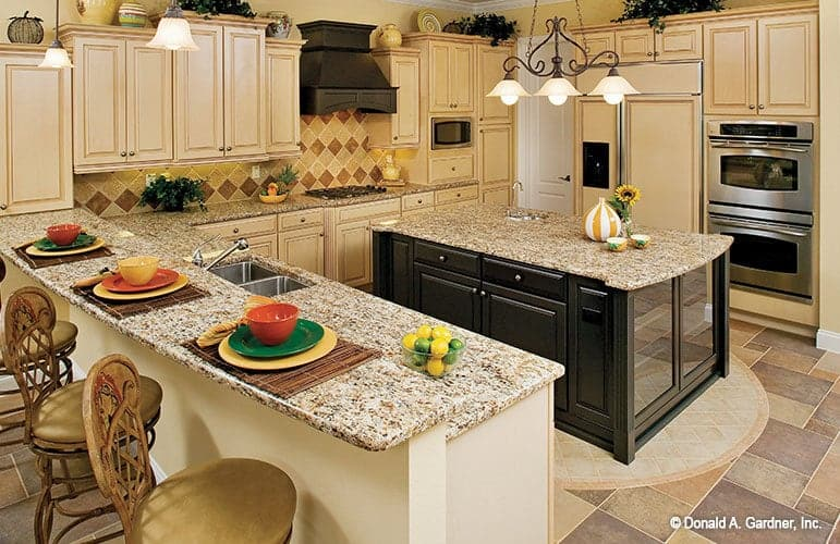 The kitchen is equipped with cream cabinetry, granite countertops, and an immense central island fitted with a sink.