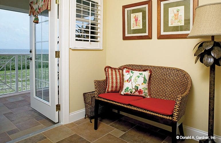 Sitting area with a cozy cushioned bench, a rattan floor lamp, and glazed doors that open out to the balcony.