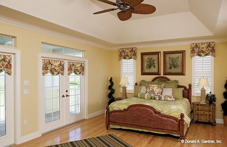The master suite has a gorgeous tray ceiling, yellows walls and french doors leading out to the covered porch.