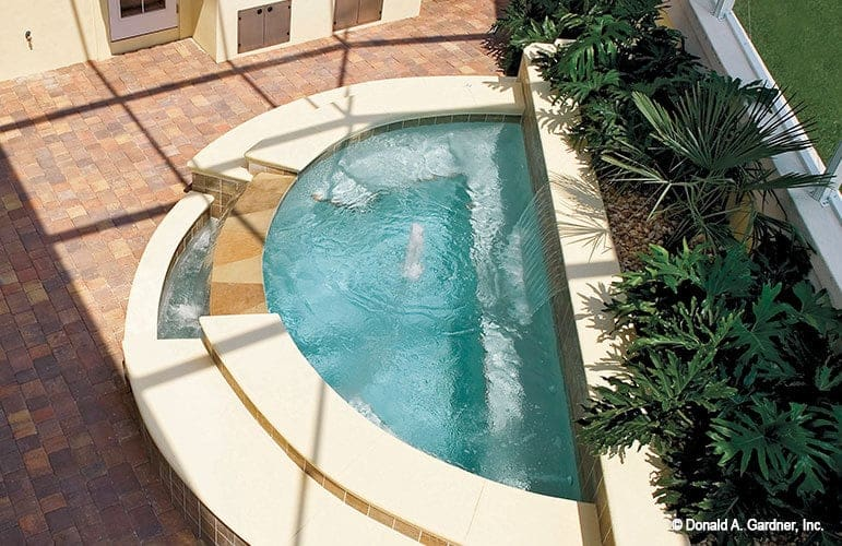 Top view of the backyard's water feature attached to the retaining wall filled with lush green plants.