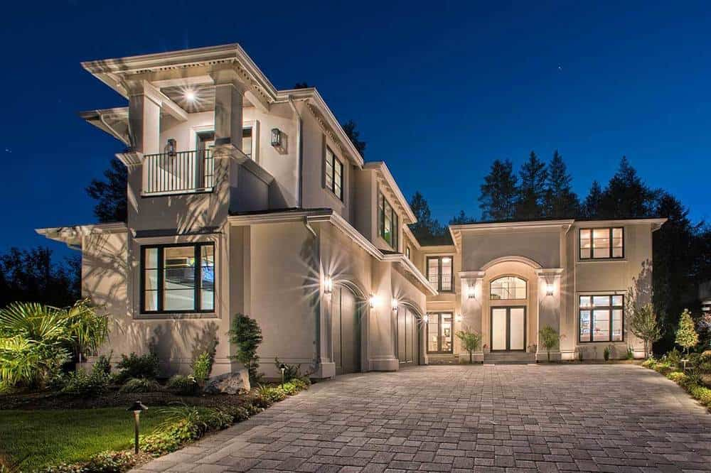 This luxurious two-story Mediterranean-style home glows warmly with its yellow exterior lights that pairs perfectly with its beige arches and pillars complemented by a gray stone brick driveway.