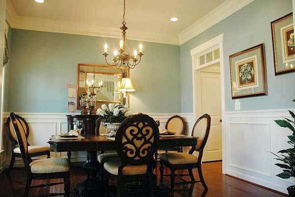Formal dining room with dark wood dining set and light blue walls adorned with a gilded mirror, framed artworks, and white wainscoting.