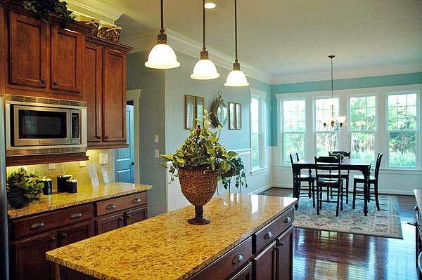 The granite top island is illuminated by warm glass dome pendants along with natural light that streams in through the white-framed windows by the breakfast nook.