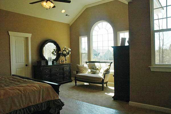 Master bedroom with beige carpet flooring and a vaulted ceiling mounted with recessed lights and a fan.
