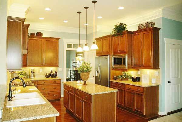 The kitchen is equipped with a double bowl sink, granite countertops, and wooden cabinetry matching the center island.