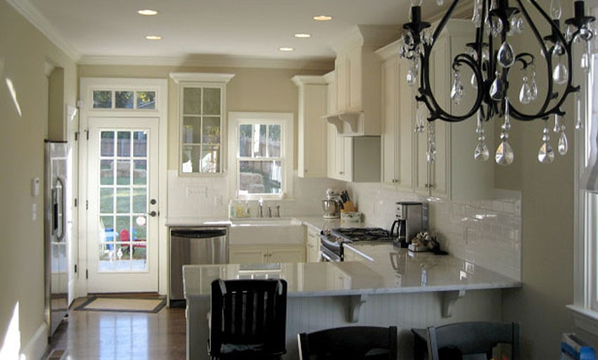 The kitchen offers stainless steel appliances, a farmhouse sink, beadboard peninsula, and bespoke cabinets that blend in with the beige walls.