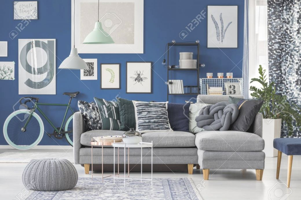 Grey Pouf On Carpet And Lamps Above Grey Couch In Living Room.. for Blue And Grey Living Room