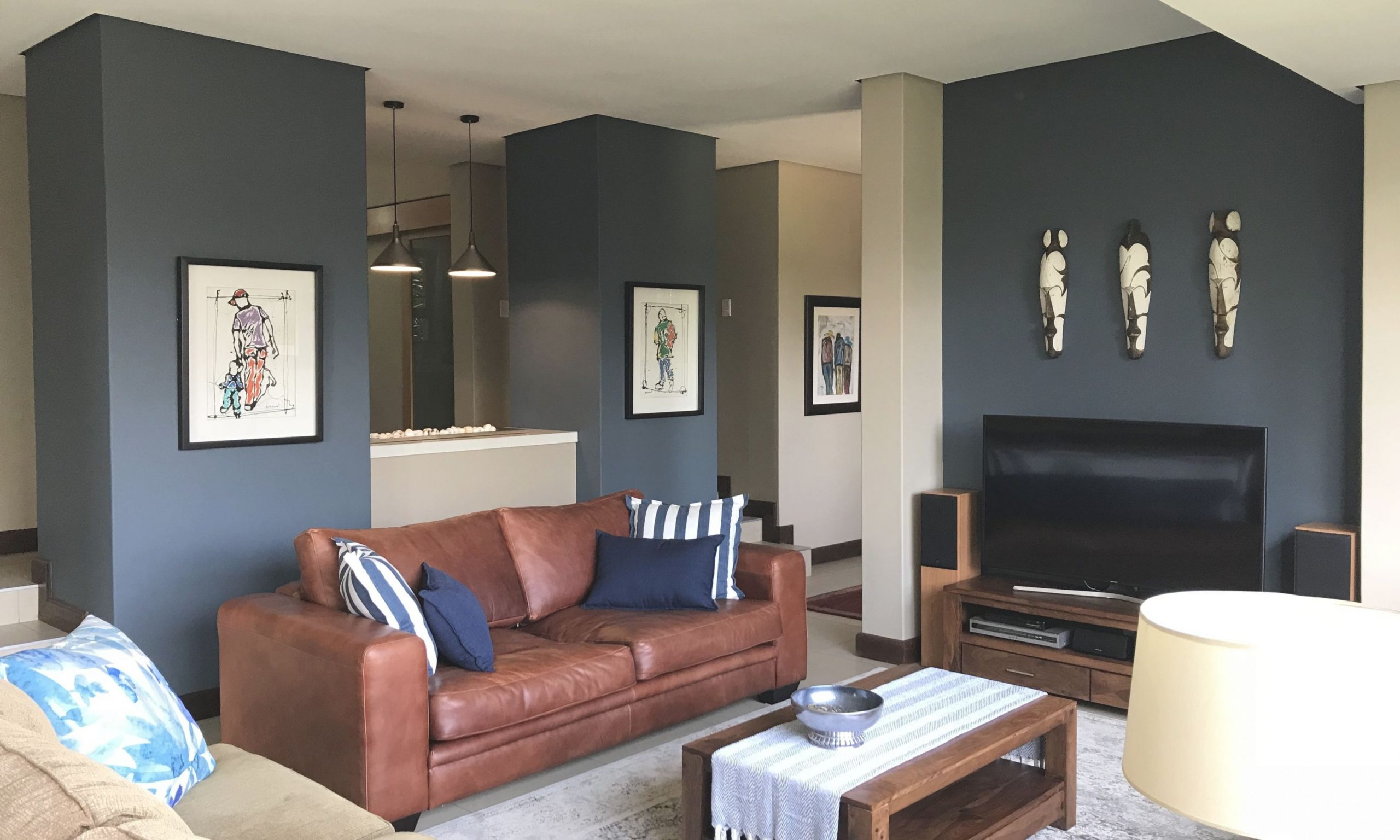 Living Room With Tan Leather Couch And Indigo Blue Walls within Blue And Tan Living Room