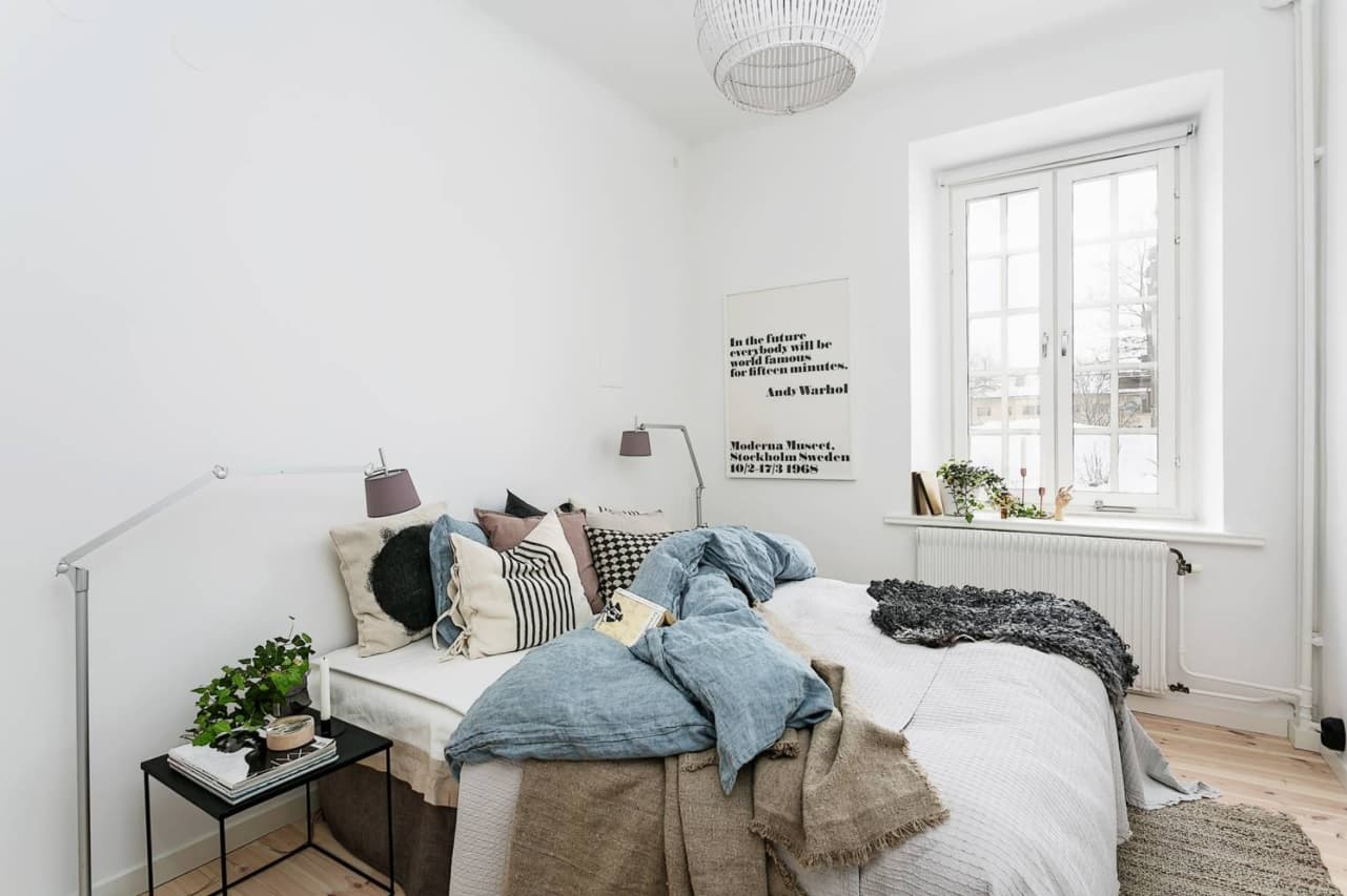White minimalistic interior of the bedroom with large bed