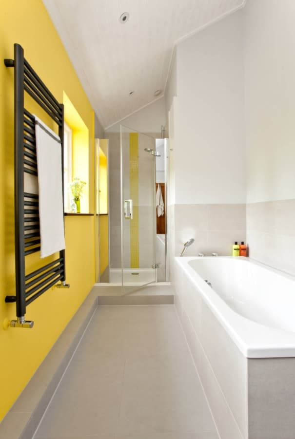 Making the Most of a Small Bathroom. Nice modern design in the compact space with accent yellow wall and black wall heater