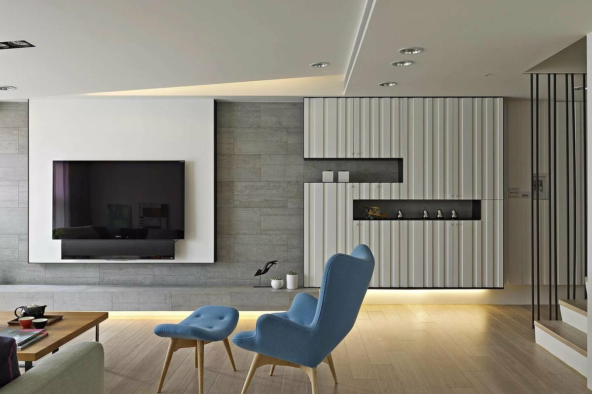 Great design with blue chair group and low lighting of the accent wall with modern inlays